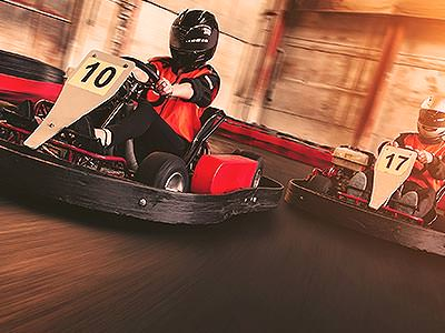 Close up on the front of two people, racing on an indoor track in go karts