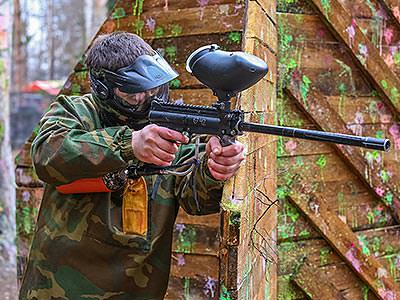 A man standing next to a wooden barricade, holding his paintball gun