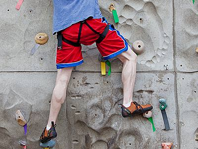 The back of a man's legs, climbing an indoor wall