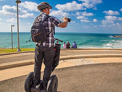 A man driving a segway along the coast as he attempts to take a photograph