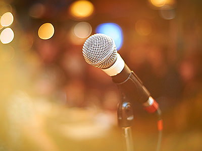 A microphone with spotlights in the background