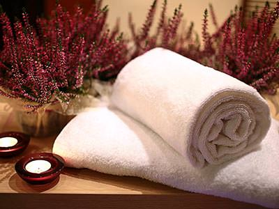 Two towels rolled up with some small plants in the background and candles on the side
