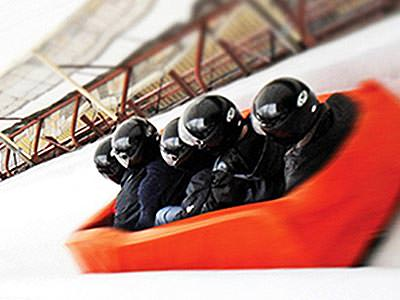 Five people sat in a red soft bobsleigh on an ice track