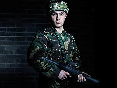 A man in camouflage clothes and hat holding a laser gun
