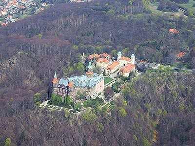 An aerial view of a castle surrounded by dense woodland