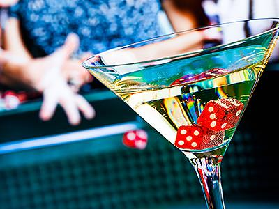 A martini glass filled with drink and with two red dice in, people are playing craps in the background