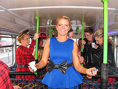 A woman in a blue top posing on a bus, with women in the background