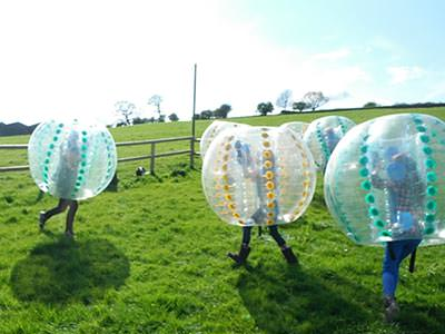 Four people in zorbs, playing on an outdoor field
