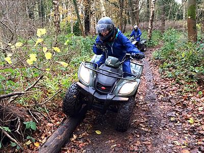 A man driving a quad bike through the forest