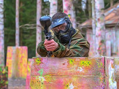 A man aiming his paintball gun at the camera, whilst sheltering his lower half with a wooden barrier