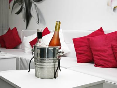 A metal ice bucket with two bottles of wine in, in front of a lounge-style seating area