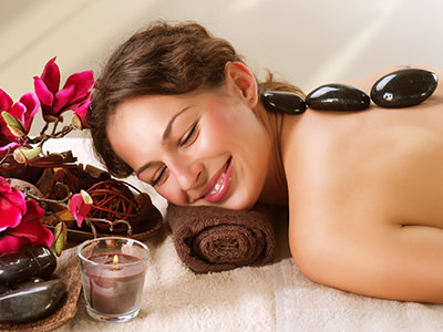 A woman on a massage table surrounded by plants and candles, with hot stones on her back