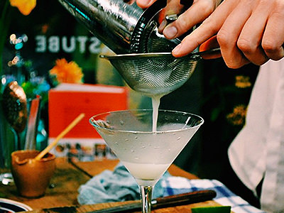 A pale cocktail being double strained into a martini glass