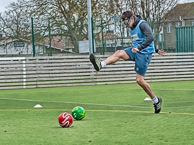 A man in a blue sports bib and shorts, attempting to kick two footballs whilst wearing goggles on an outdoor pitch