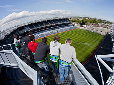 A group of people looking out from a rooftop gantry at Croke Park