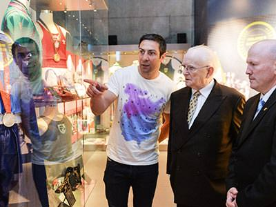 A man pointing out memorabilia in a cabinet to two men in dark suits