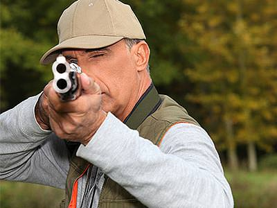 A man aiming a shotgun to the camera