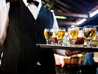 A a person serving glasses of alcohol on a plate