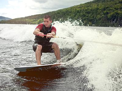 A man riding over the waves on a cable ski