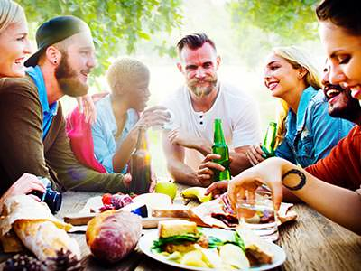 Six people sitting on a picnic bench outside, eating food and drinking from bottles