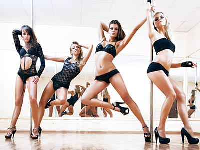 Four women in black underwear, holding on to a pole and posing in a studio with a mirrored wall in the background