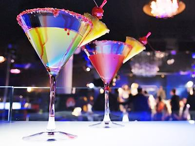 Two cocktails in martini glasses with a slice of pineapple on the side of the glass