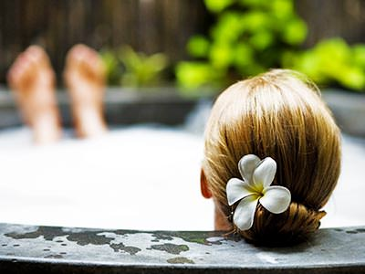 The back of a woman's head with a flower in her hair, lying back in an outdoor Jacuzzi
