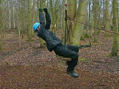 A man climbing on a low ropes course in the forest