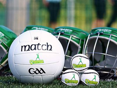 A gaelic football alongside three small balls, placed in front of green helmets