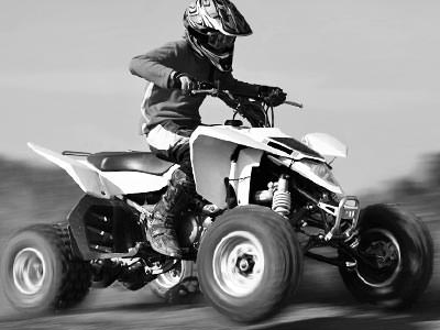 A black and white image of a man driving a quad bike outdoors