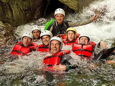 Six people with an instructor in the water, all wearing helmets and life jackets