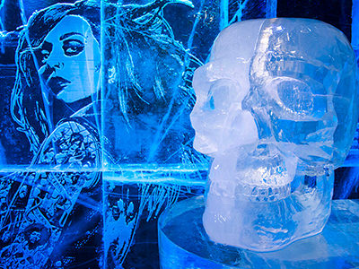A woman on the wall of ICEBAR, London, and an ice sculpture of a skull