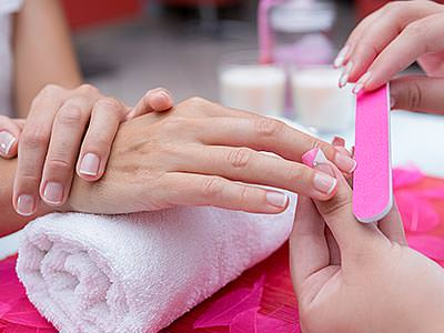 A woman having her nails filed by a beautician