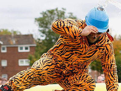 A man in a tiger onesie and a blue helmet