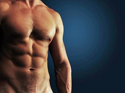 A naked male torso to a blue backdrop