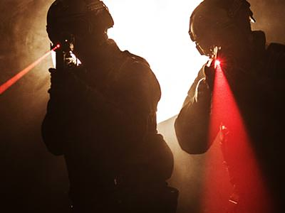Two male silhouettes aiming red lasers with laser guns