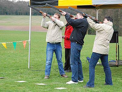Three men aiming with shotguns