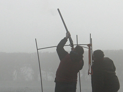 A man aiming a shotgun to the sky with a man looking on, to a foggy backdrop