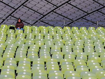 One person sitting in the seats in Munich's Olympic Stadium