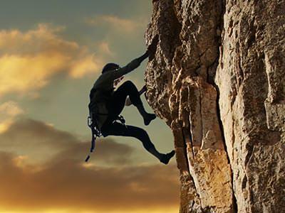 A person climbing up a vertical rock face