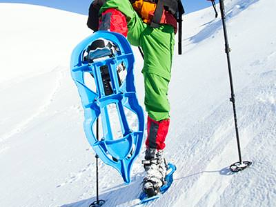 A person wearing green trousers and blue snow shoes climbing up a snowy surface