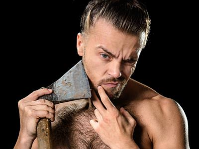 A man attempting to shave using an axe