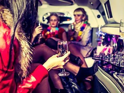Three girls in a party bus, with champagne flutes in their hands and flower garlands around their necks