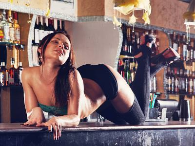 A woman on the bar, wearing a bra, knickers and suspenders