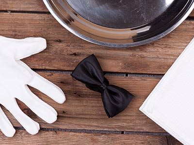 A glove and a bow tie on a wooden table