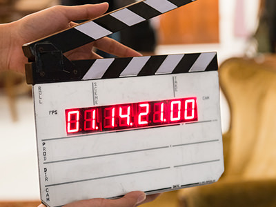 A hand holding a clapper board with red numbers on it