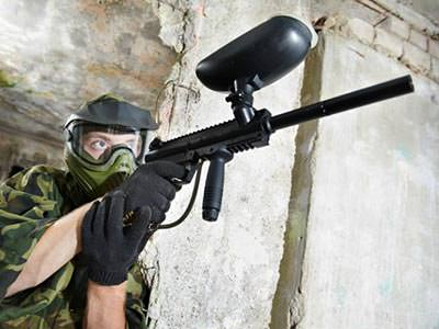 A man in camouflage gear, holding a paintball gun to a backdrop of a brick wall