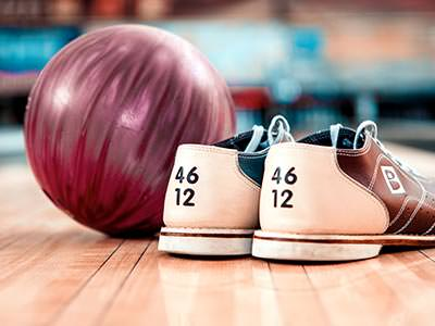 Bowling shoes next to a red bowling ball, with a blurred bowling alley in the background