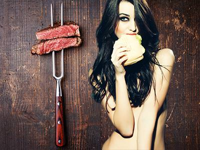 Two pieces of uncooked meat on a BBQ skewer and a naked girl eating a burger
