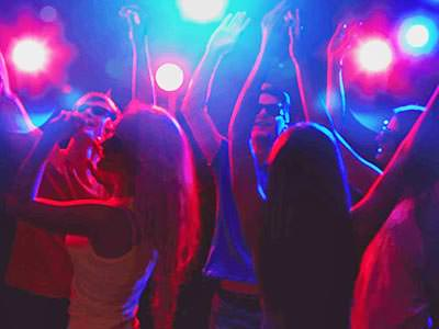 People silhouettes, dancing to a backdrop of pink and blue lights